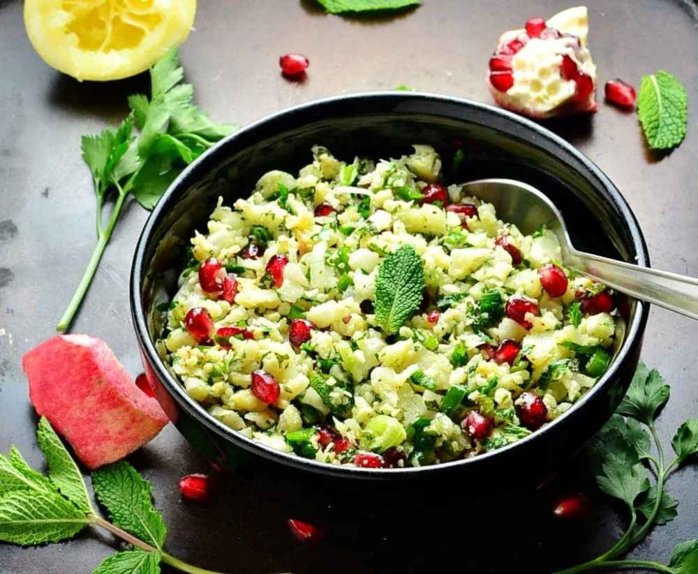 Side view of roasted cauliflower tabbouleh salad with pomegranate seeds and spoon in black bowl, with herbs and pomegranate seeds scattered around.