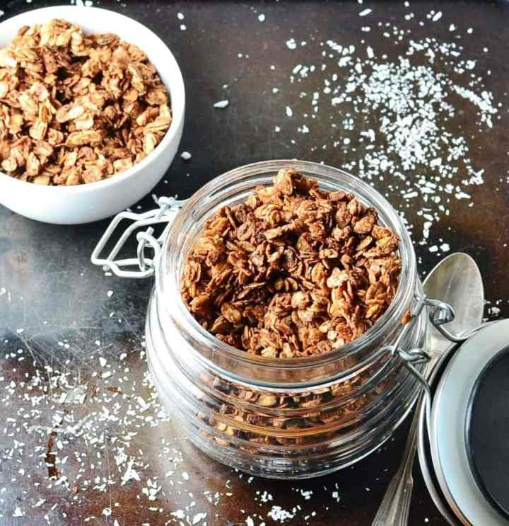 Top down view of chocolate granola in open jar with spoon to right and sea salt on top of dark shiny surface.