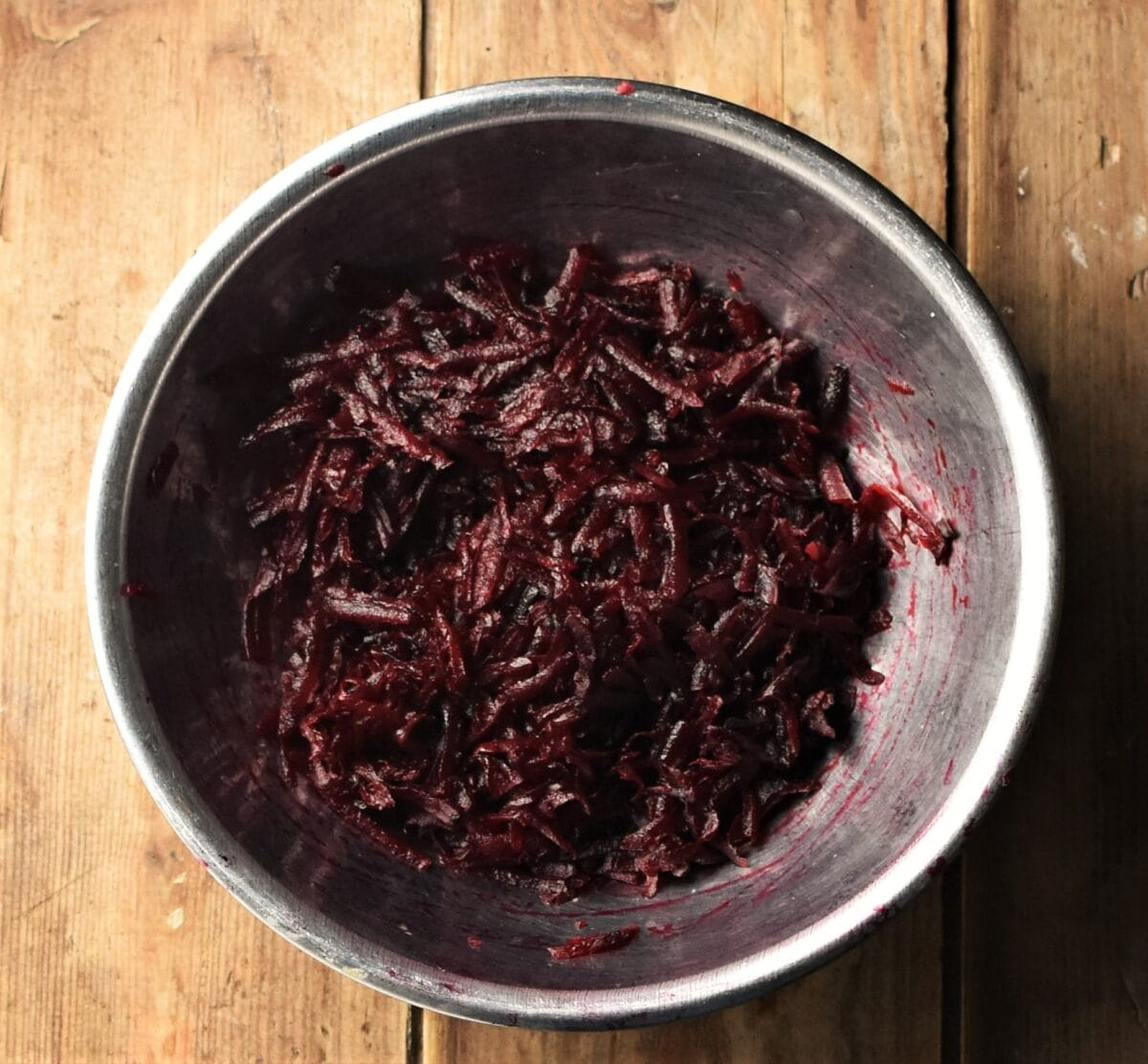 Grated beetroot in metal bowl.