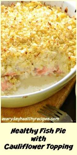 Healthy fish pie with cauliflower topping in white oval dish on top of wooden board with fork.