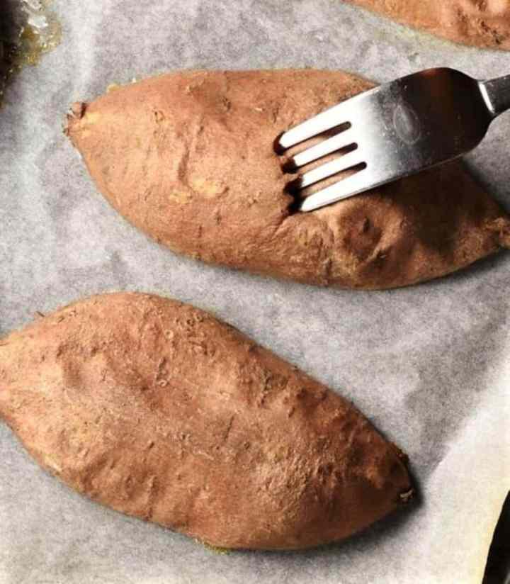2 halves of sweet potato with fork on parchment.