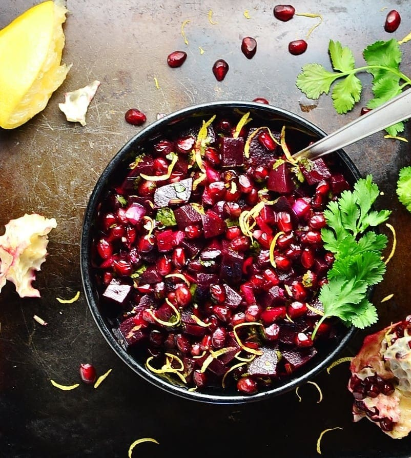 Top down view of beets pomegranate salad with spoon in black bowl, with lemon and pomegranate seeds in background.