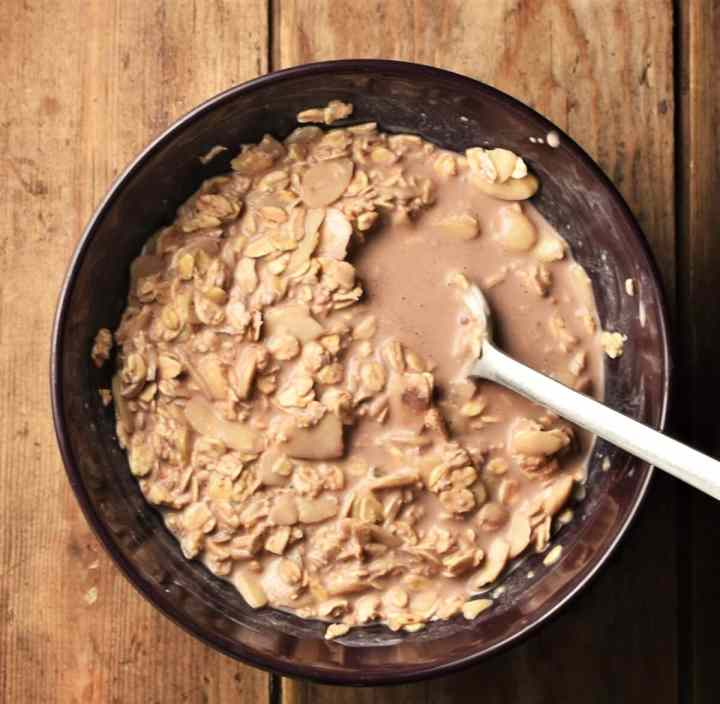 Oats mixture with milk and cocoa in bowl with spoon.