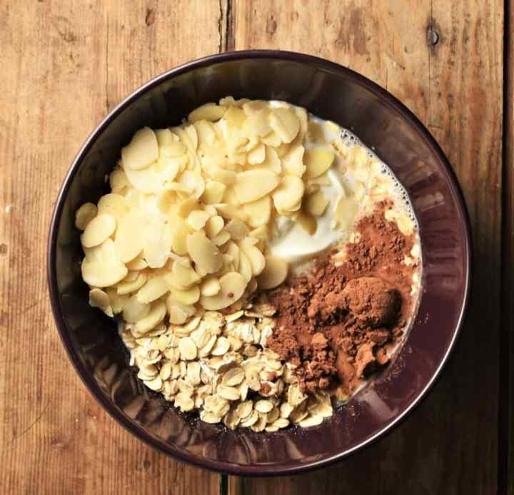 Oats, flaked almonds, milk and cocoa in bowl.