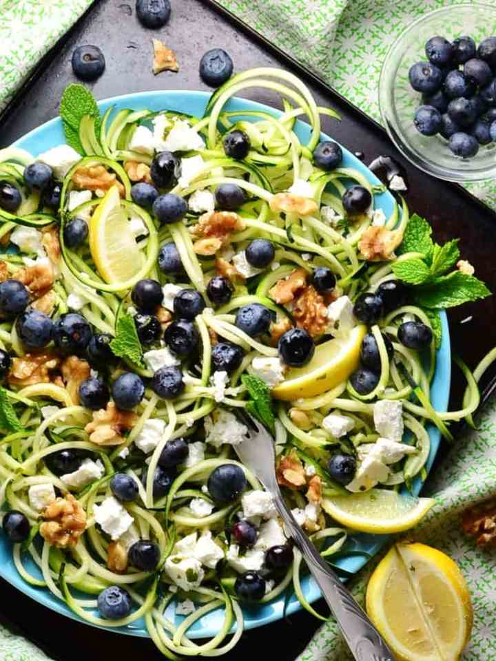Top down view of blueberry feta salad with spiralized zucchini and lemon wedges on top of blue plate on dark tray, with blueberries in small dish and green cloth in background.