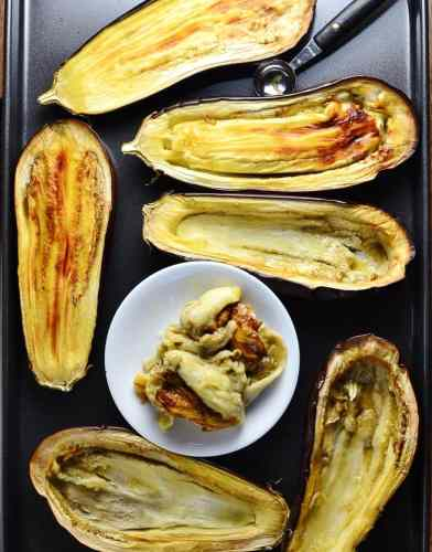 Eggplant halves on even tray with small white plate.