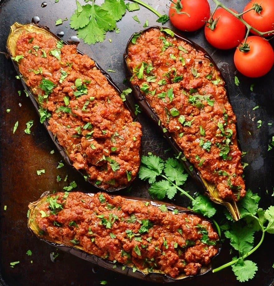 Top down view of baked stuffed eggplant with herbs and tomatoes on the vine on oven tray.