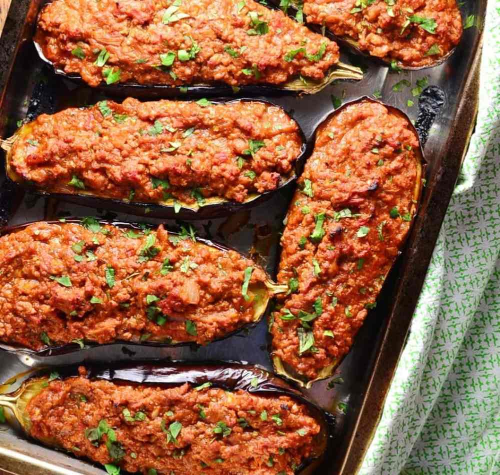 Top down view of stuffed eggplant on oven tray with green cloth to right.
