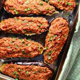 Top down view of stuffed eggplant on oven tray with green cloth.