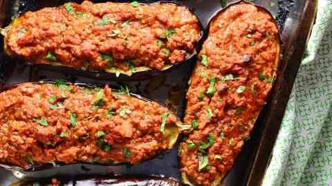 Top down view of baked stuffed eggplant on oven tray with green cloth.