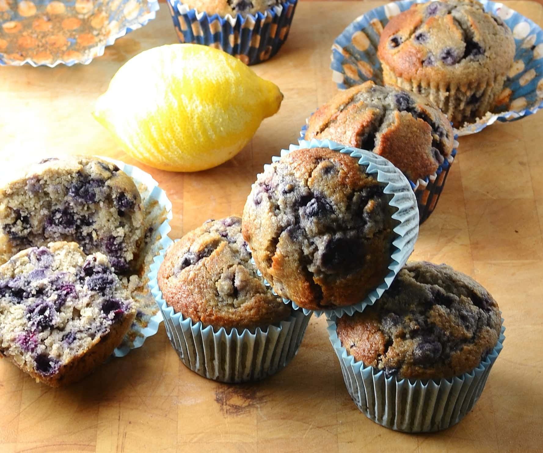 Close-up view of blueberry muffins with lemon in background on top of wooden table.