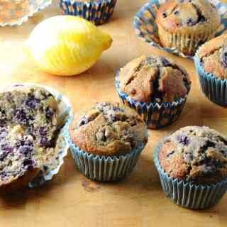 Blueberry muffins with maple syrup in blue paper cases with lemon on wooden surface.