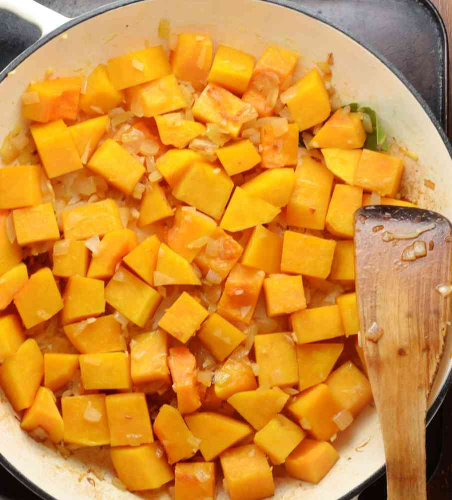Top down view of cubed butternut squash with onions in large shallow white dish with wooden spoon.