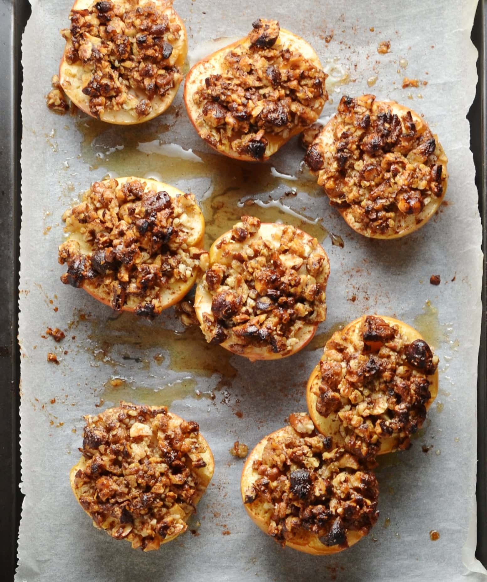 Baked apple halves with chopped pecans on top of paper.