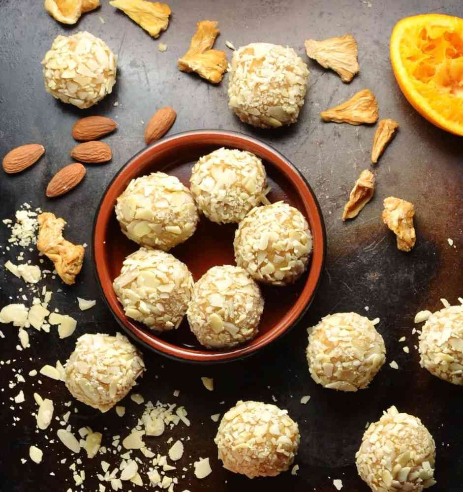 Top down view of almond energy balls inside round brown dish and on top of dark surface, together with almond flakes, almonds, dried pineapple and orange peel.
