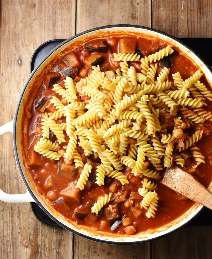 Eggplant with tomato sauce with fussili pasta in large shallow white pan with wooden spatula.