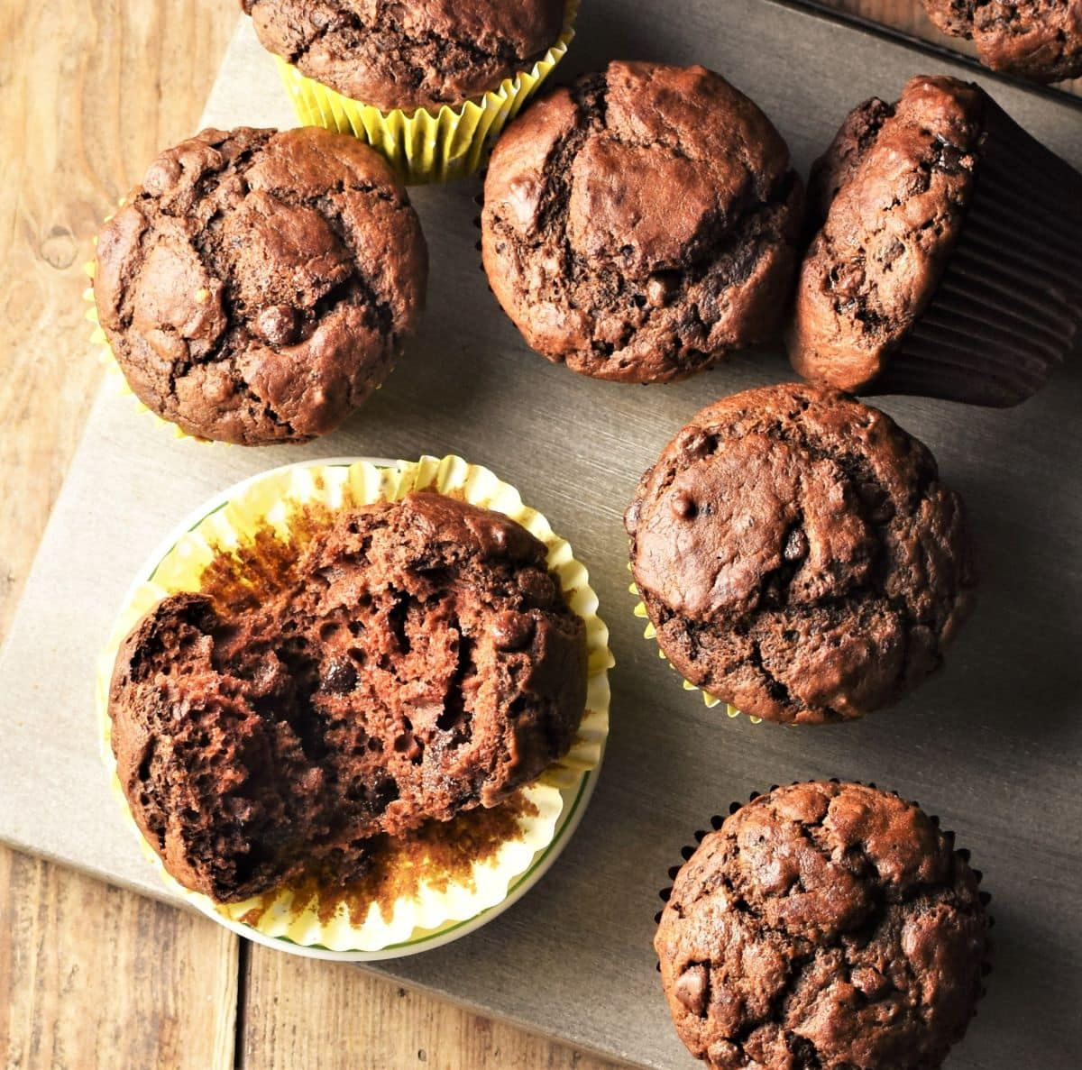 Pumpkin chocolate muffins in paper liners on top of grey board.