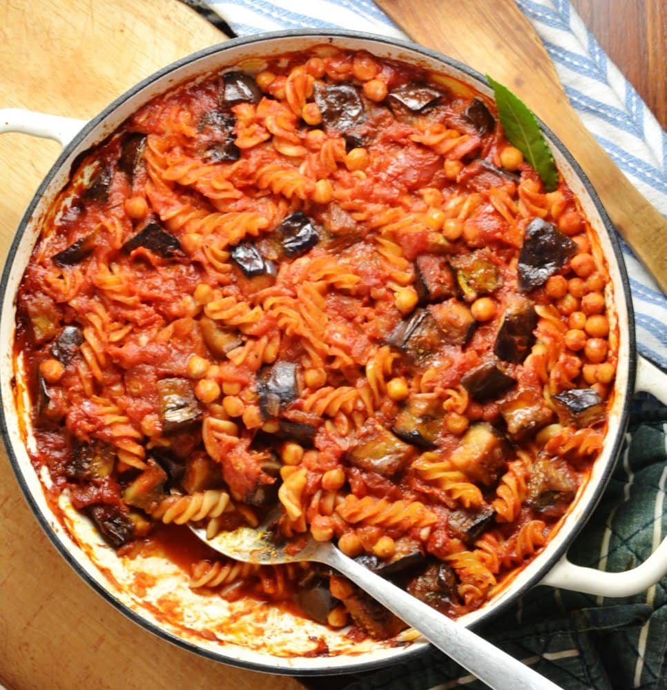Side view of eggplant pasta bake in large white casserole dish with spoon on wooden board with stripy blue cloth.