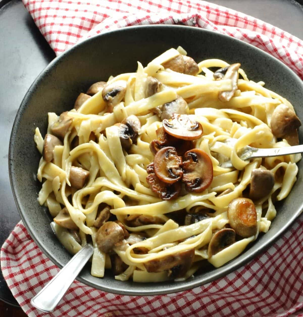 Mushroom tagliatelle pasta in dark grey bowl with forks and red-and-white checkered cloth.