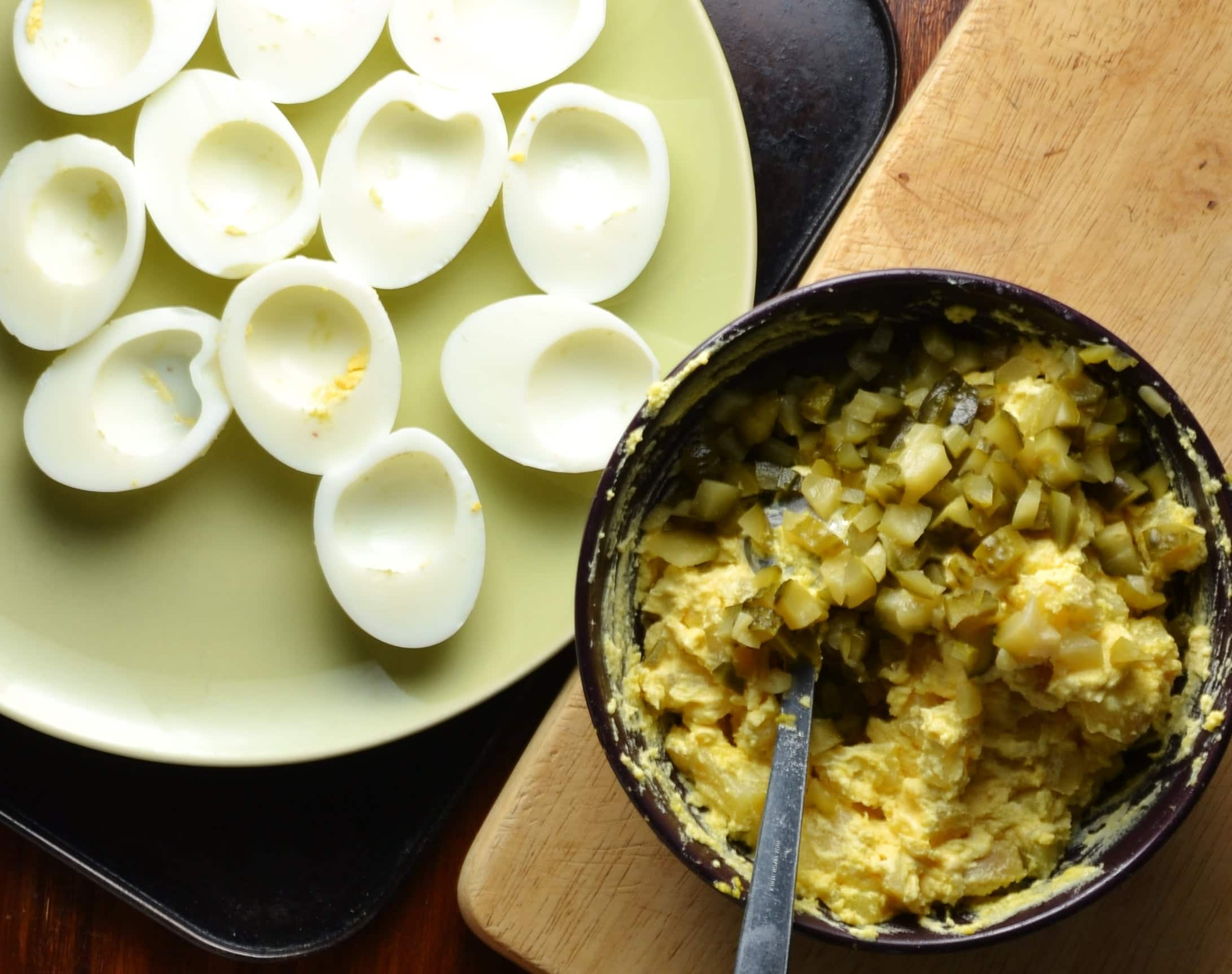 Potato salad filling in black bowl with spoon on cutting board and egg halves without yolks on green plate.