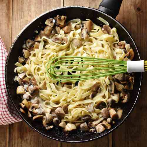 Pasta with mushrooms and whisk inside large pan.