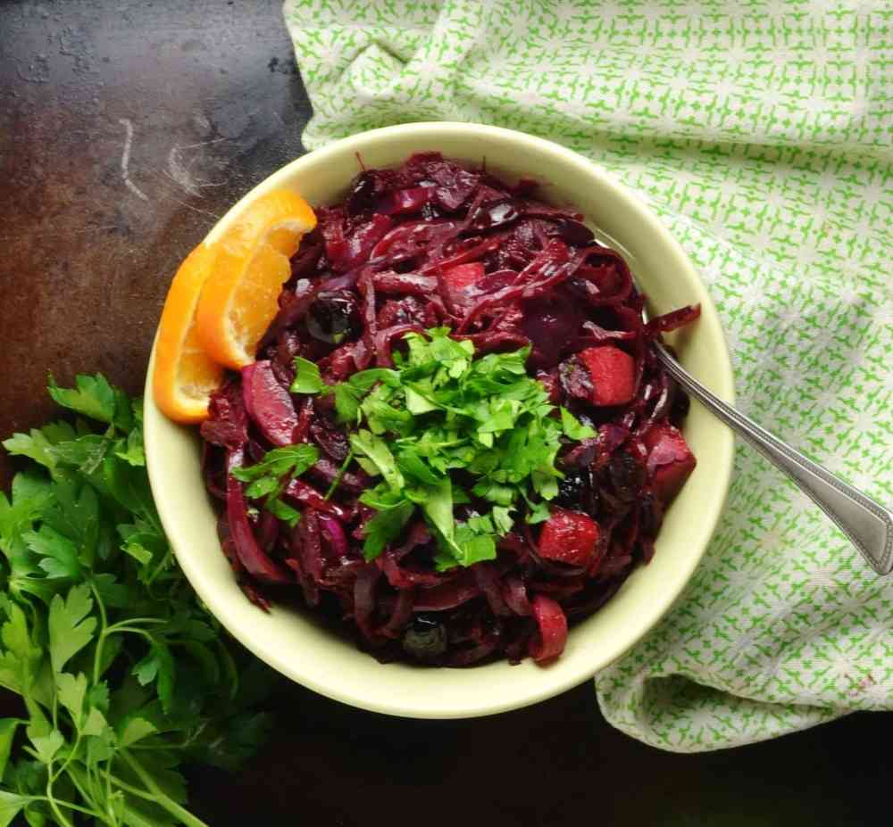 Top down view of chopped red cabbage in green bowl with spoon, herbs and green cloth.