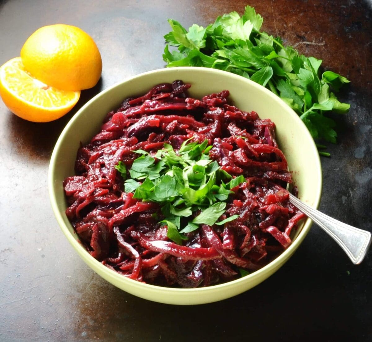 Braised red cabbage in green bowl with spoon and clementine and herbs in background.