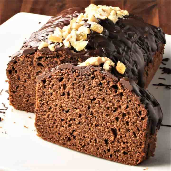 Side view of gingerbread loaf cake topped with chocolate and nuts.