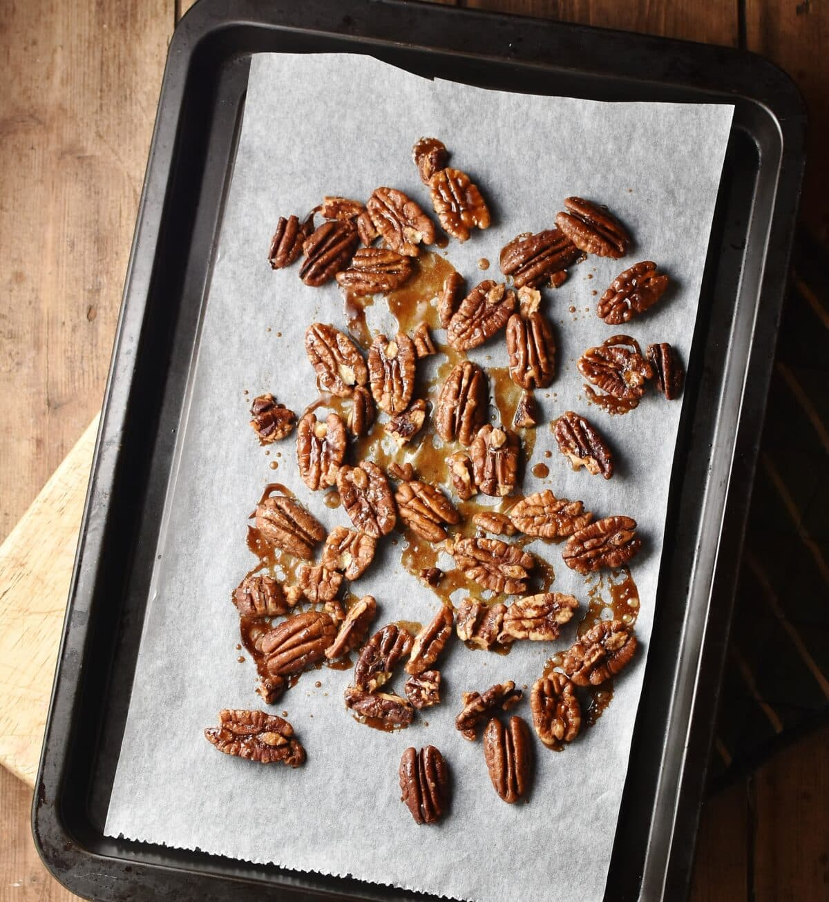 Roasted pecans on top of baking sheet lined with parchment paper.