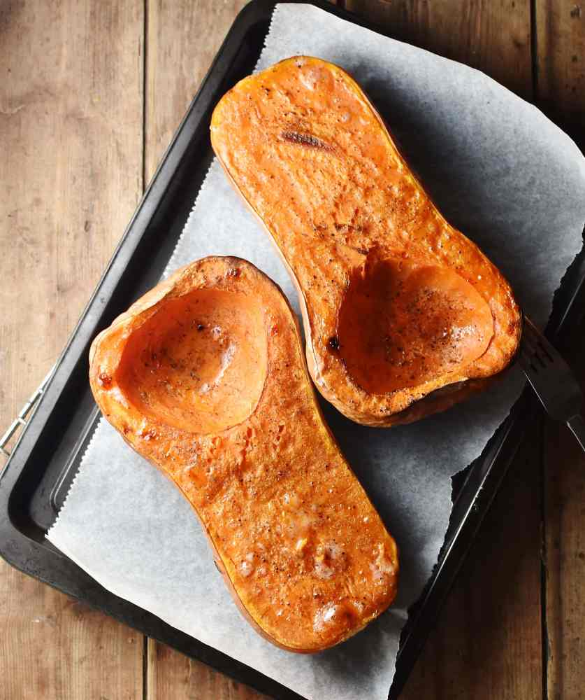 Roasted butternut squash halves on top of baking sheet lined with parchment paper.