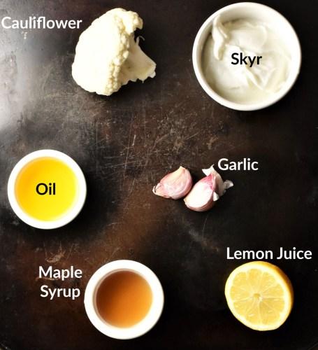 Cauliflower dip ingredients on top of dark surface.