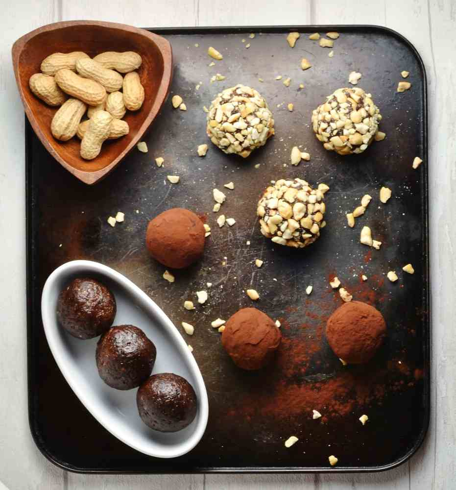 Top down view of Chocolate Peanut Butter Energy Balls in white dish with peanuts in brown dish on metallic tray.
