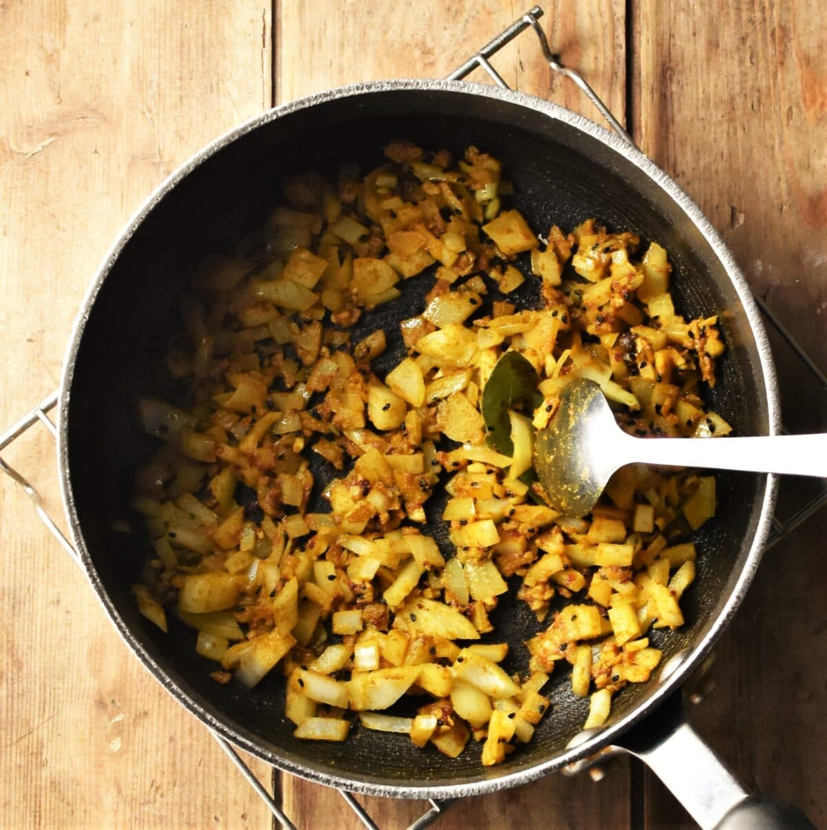Chopped onions and spices in large pot with spoon.