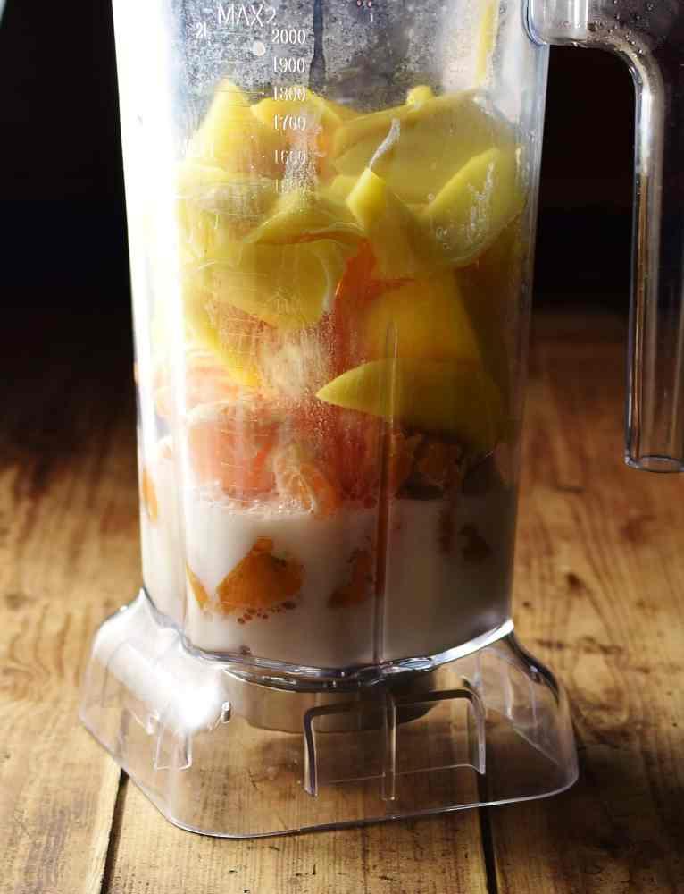 Chopped mango, tangerine, sweet potato and milk in blender.
