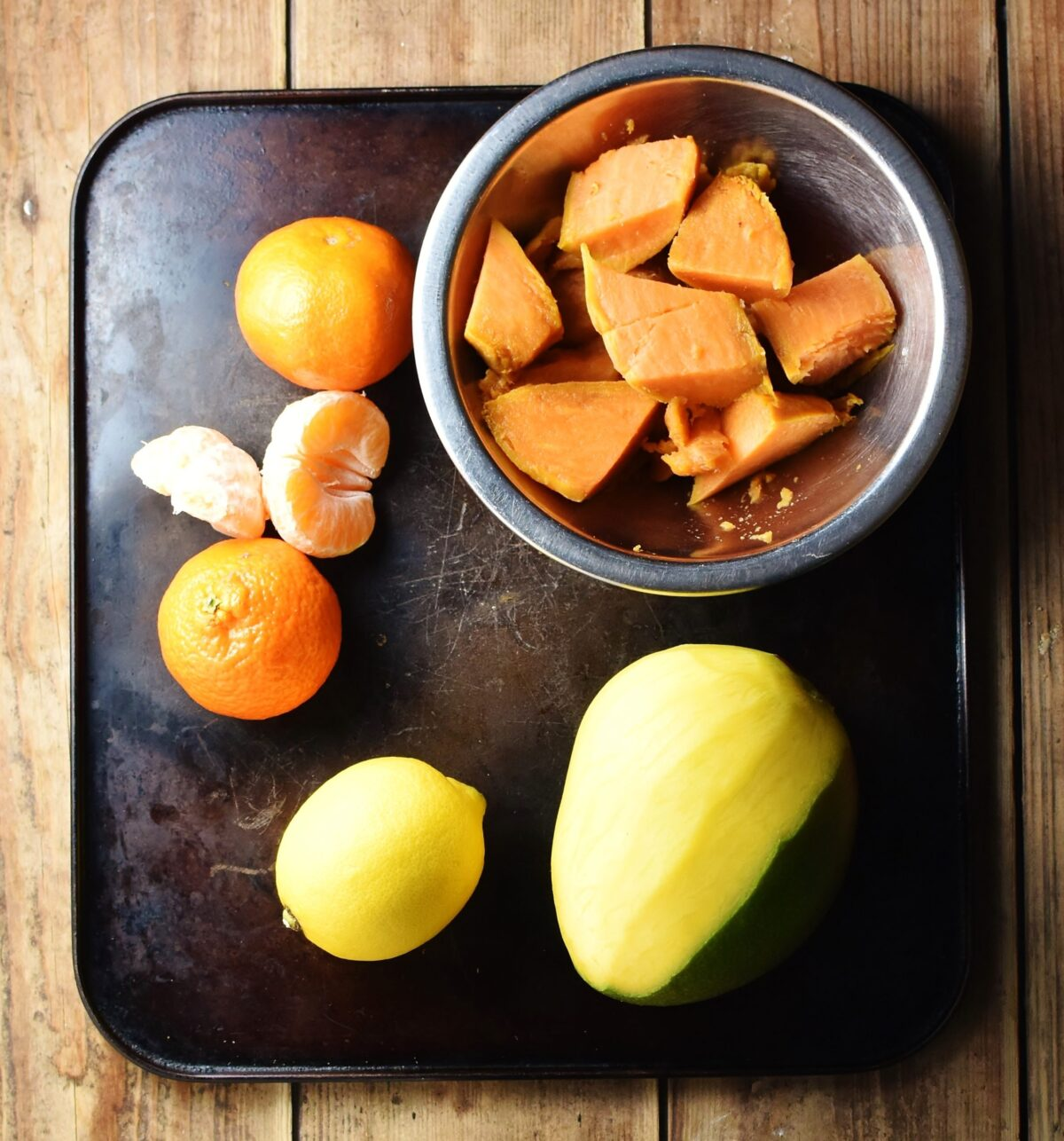 Tangerines, lemon, mango and chopped sweet potato in metal bowl.