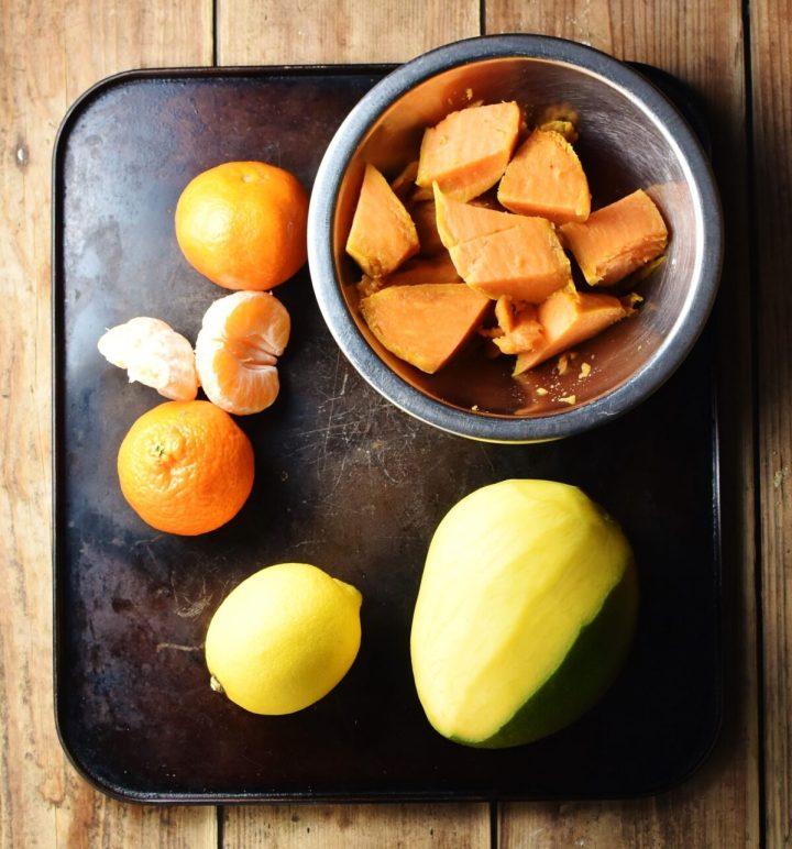 Tangerines, lemon, mango and chopped sweet potato in metal bowl.