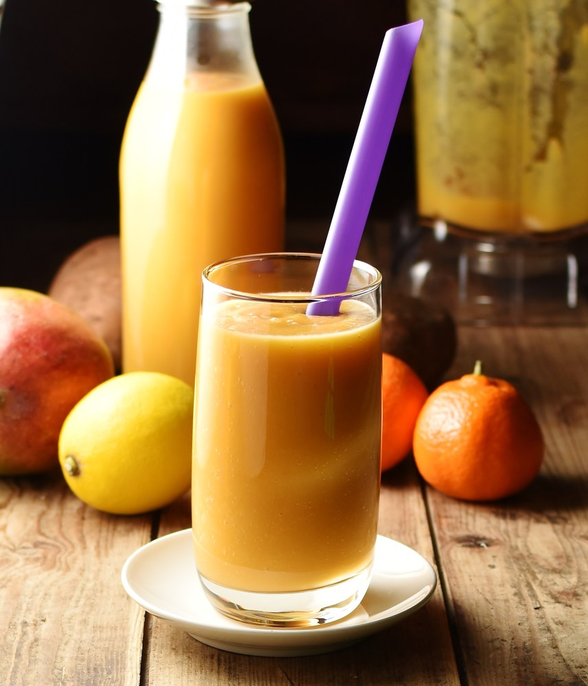 Sweet potato smoothie in glass with purple straw, lemon, tangerine, mango, smoothie in bottle and blender in background.