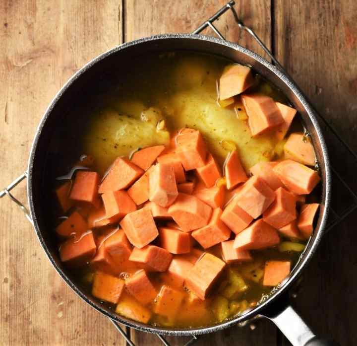 Cubed sweet potato in large pot with soup.