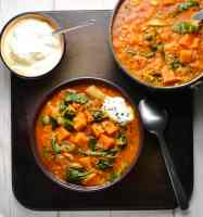 Top down view of mulligatawny soup in bowl and saucepan with small bowl of yogurt with spoon on oven tray.