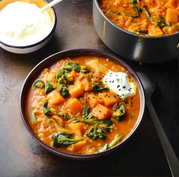 Chicken mulligatawny soup in purple bowl, black saucepan, with spoon and yogurt in blue bowl on oven tray.