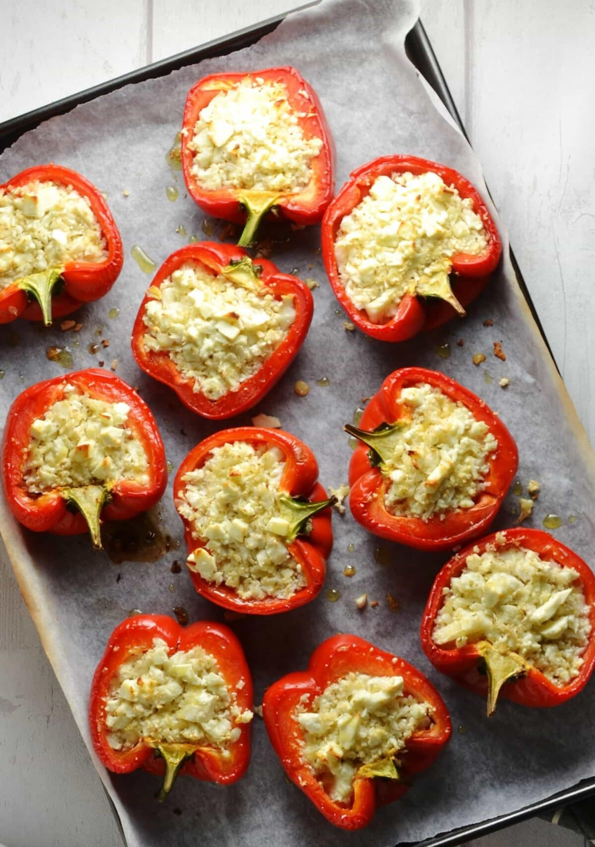 Cauliflower rice stuffed red peppers on baking tray lined with non-stick paper.