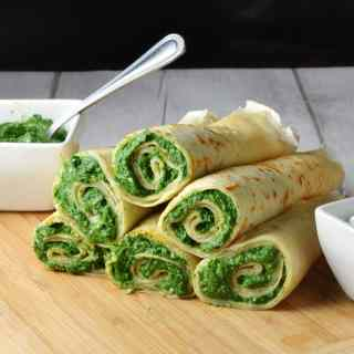 Crepes with spinach filling on light wooden board with white dish with spinach mixture and spoon in background.