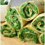Crepes with spinach filling on wooden board with spinach mixture with spoon in white dish to left.