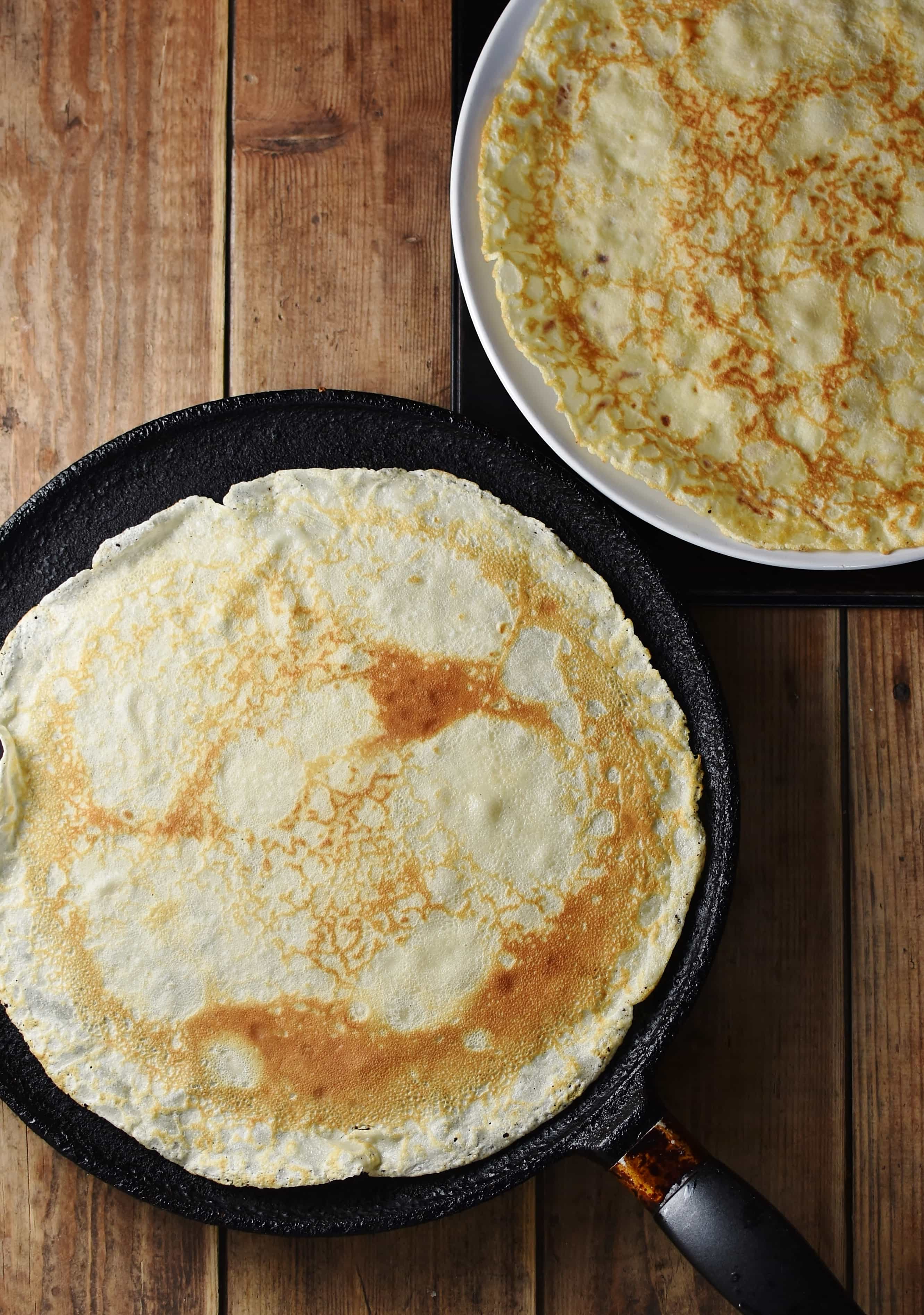 Large crepe in pancake pan and on top of large plate.