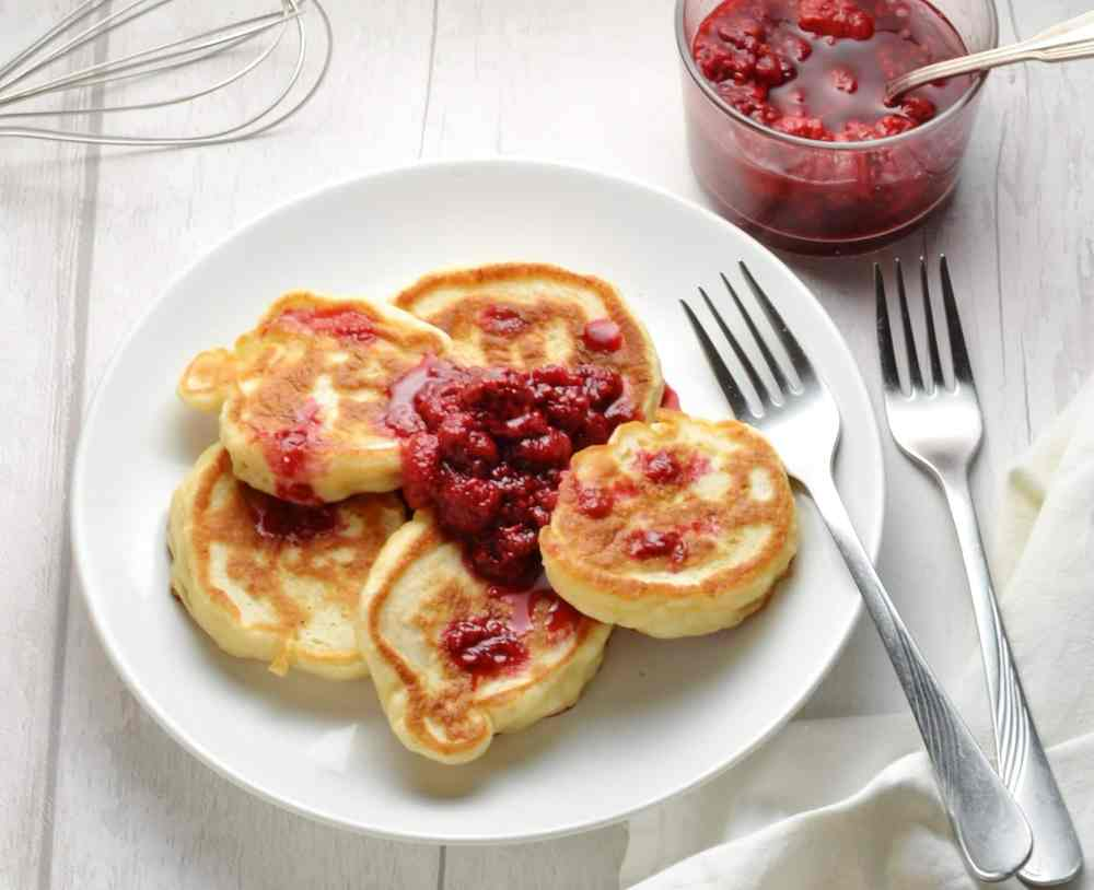 Polish pancakes on white plate with raspberry compote and forks on white table.