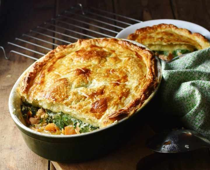 Salmon, spinach and sweet potato pie with puff pastry topping in green oval dish, with green cloth, spoon and pie in white bowl in background.