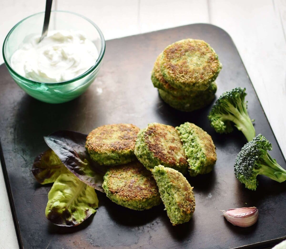 Top down view of broccoli patties on black tray with broccoli florets, garlic clove and dish with yogurt in background.