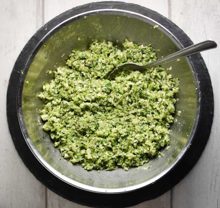 Top down view of broccoli patties mixture in metal bowl with spoon.