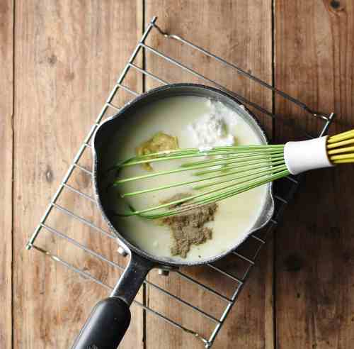 White sauce with mustard, yogurt, spices and green whisk in small saucepan.