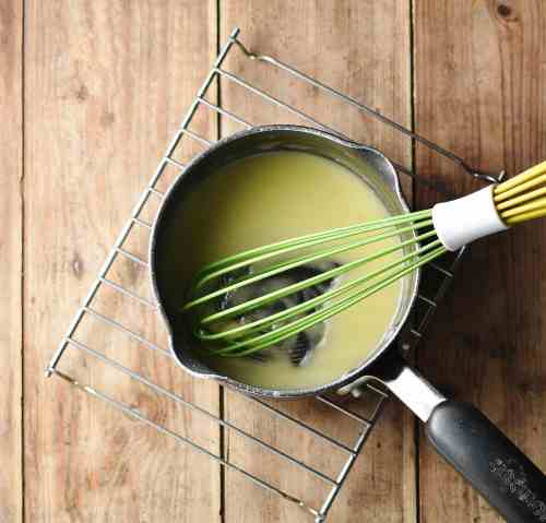 Roux sauce with green whisk in small saucepan.